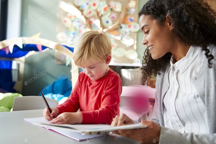 Weibliche Säuglingsschullehrerin Arbeit eins zu eins mit einem jungen weißen Schuljungen