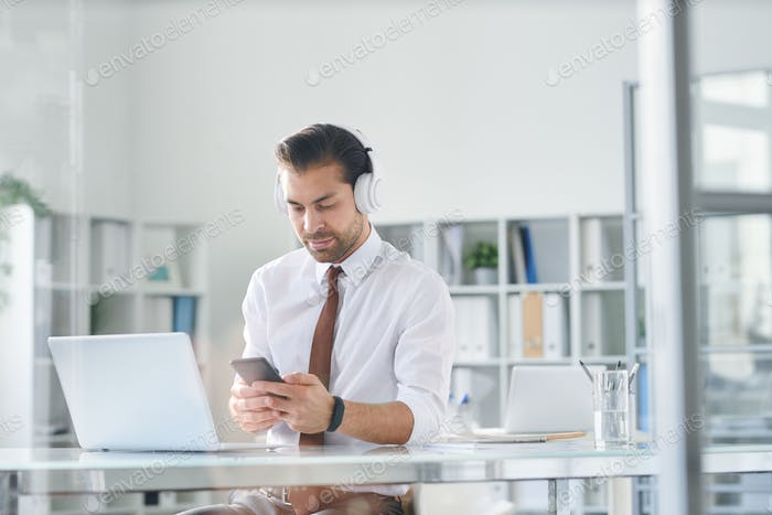 Young elegant man in headphones scrolling in smartphone