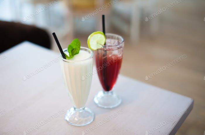 Zwei Gläser frische Limonade oder Cocktails mit Eis auf dem Tisch im Sommercafé. Flache Schärfentiefe