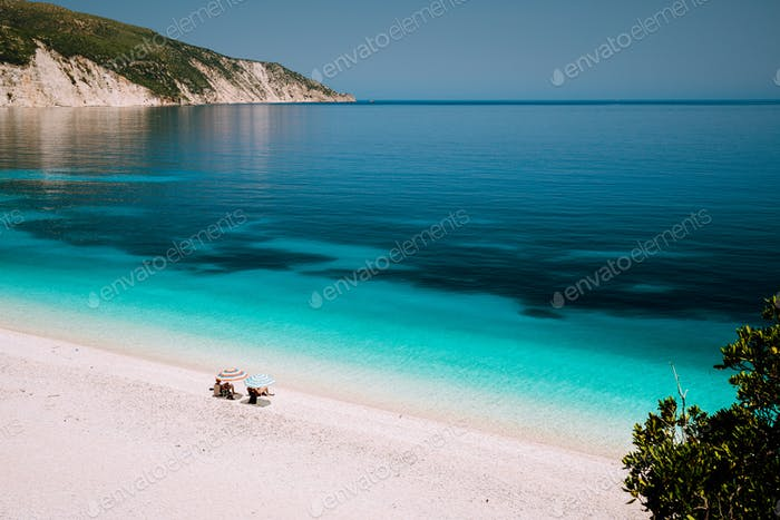 Fteri beach, Kefalonia, Greece. Summer vacation holiday. Lonely unrecognizable tourist couple hiding