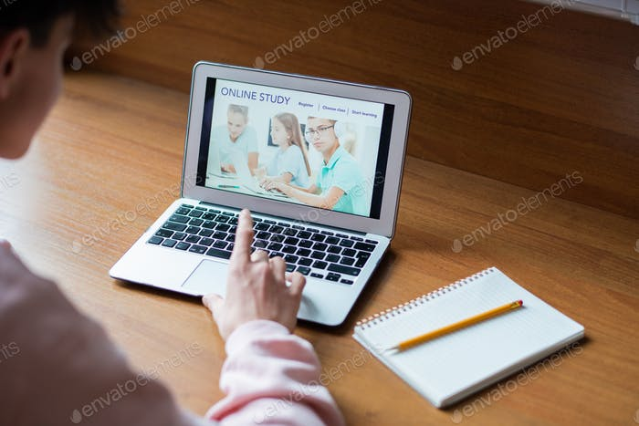 Laptop with image of schoolkids on screen and college student touching key