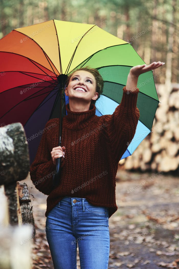 Young woman with umbrella in the autumn forest