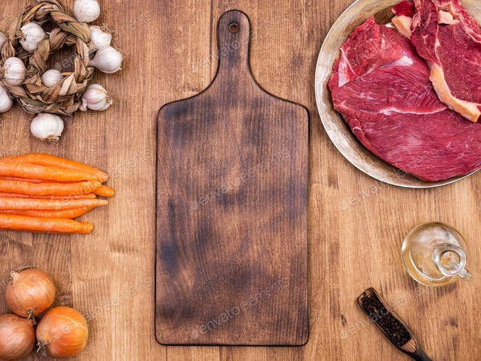 Top view of vintage cutting board next to two pieces of red meat on wooden table