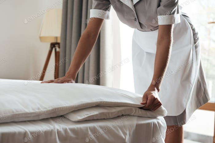 Cropped image of a chambermaid making bed in hotel room