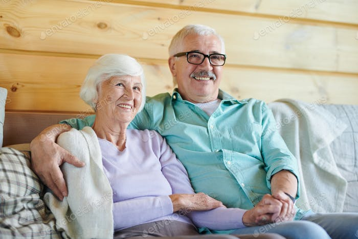Cheerful mature spouses in casualwear watching program