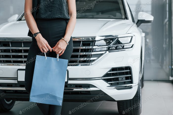Leaning on the automobile. Girl and modern car in the salon. At daytime indoors. Buying new vehicle