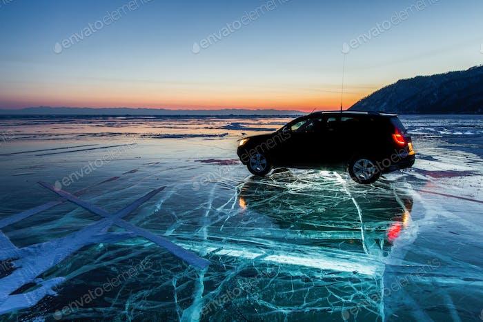 Car on the ice of Lake Baikal at sunset
