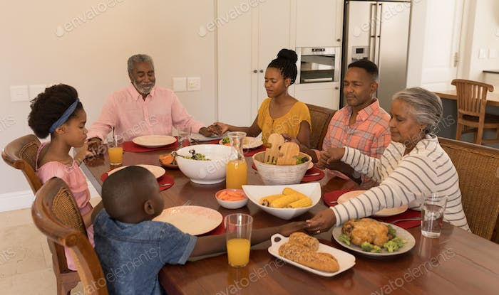 Family holding their hands and praying together before having meal on dining table at home