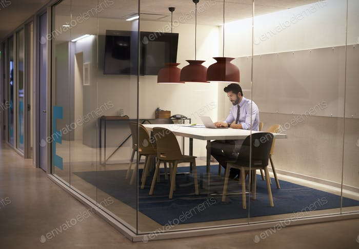 Hispanic businessman works in cubicle at corporate business