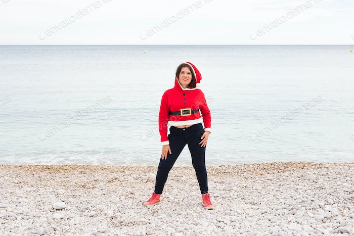 Christmas and holiday concept - Funny woman in Santa Claus costume having fan over sea background