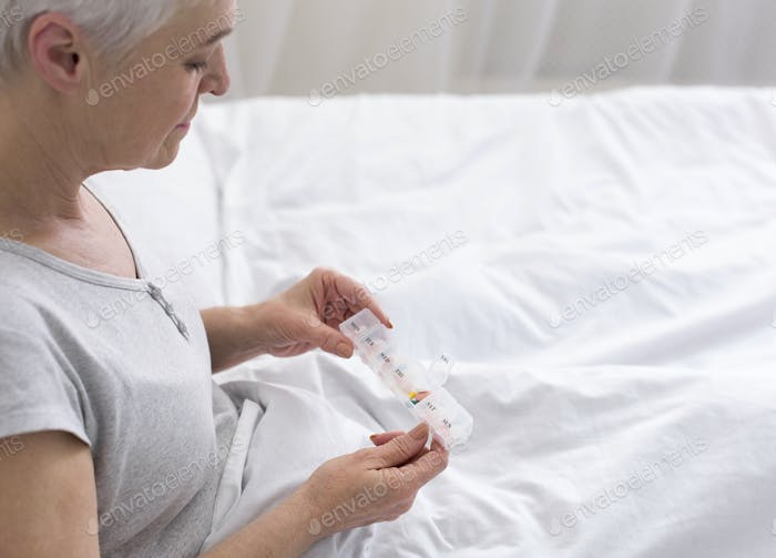 Senior lady taking pills from medical box, sitting in bed