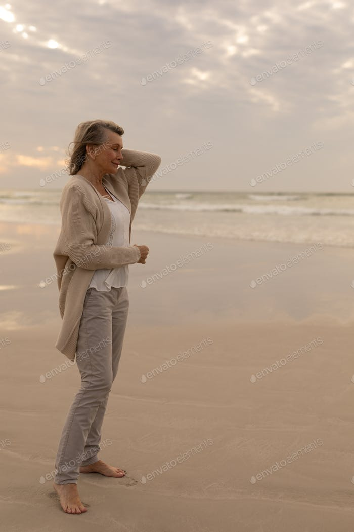 Side view of senior Caucasian woman standing with eyes closed on the beach at beach