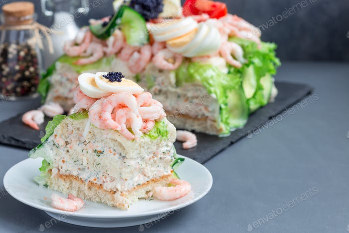 Piece of traditional savory swedish sandwich cake Smorgastorta w
