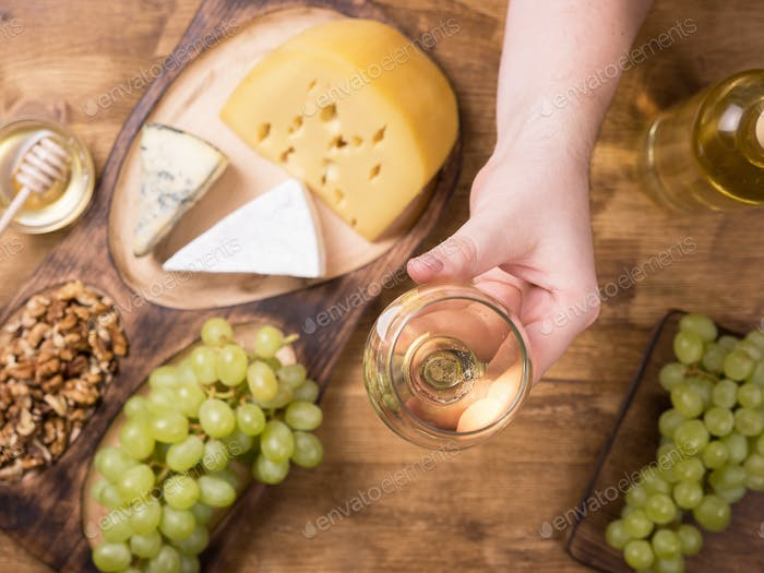 Top view of a hand holding a glass of white wine next to fresh grapes on a wooden table