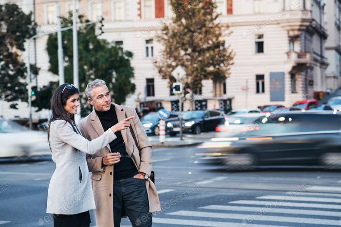 Man and woman business partners crossing road outdoors in city, talking.