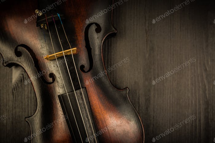 Detail of old violin in vintage style on wood background