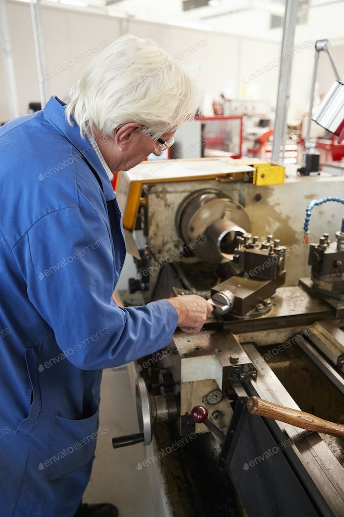 Senior engineer operating industrial machinery in a factory, vertical