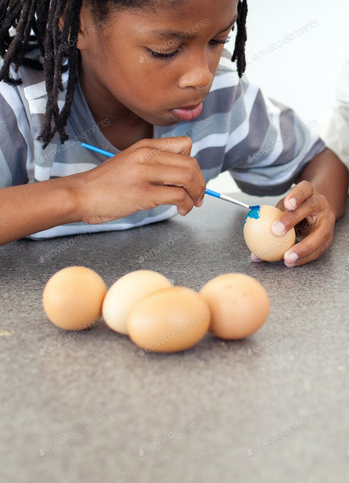 Cute Afro-american little boy painting eggs
