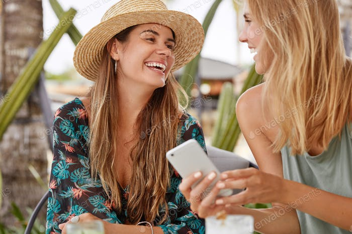 Shot of happy females have pleasant talk, use modern devices for communication in social networks, c