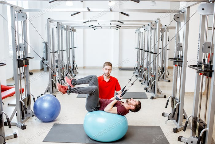 Man exercising with trainer at the rehabilitaion gym