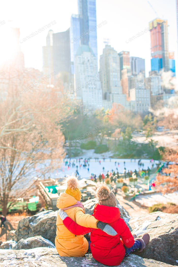 Adorable little girls with view of ice-rink in Central Park at New York City