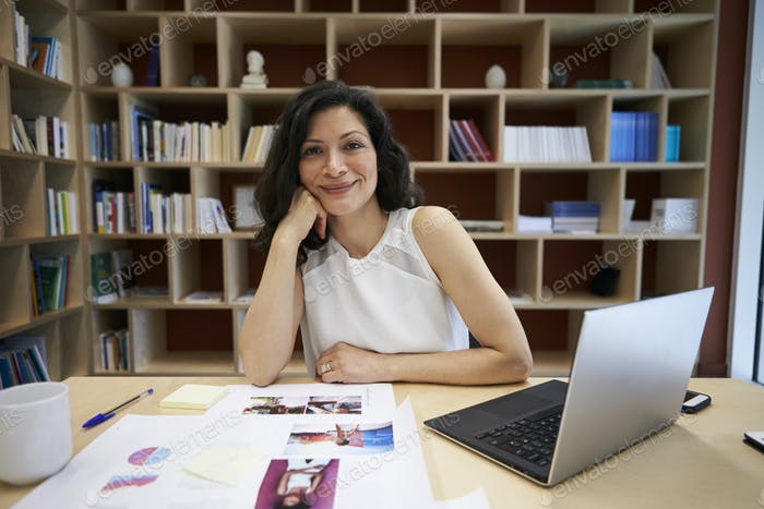 Middle aged female creative using laptop smiling to camera