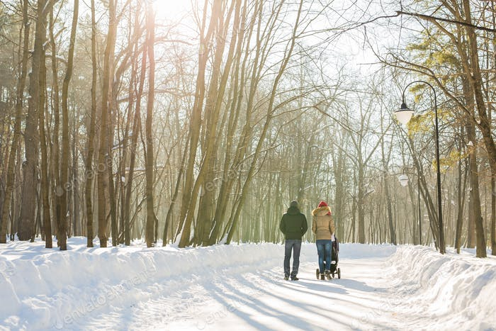 Father and mother with baby carriage in winter forest