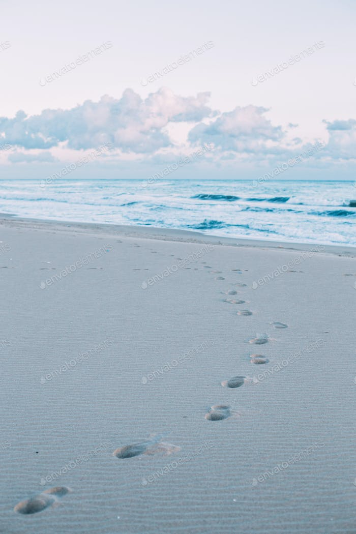 Footsteps on beautiful beach at sunrise