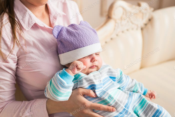 Close up of mother holding newborn baby in arms