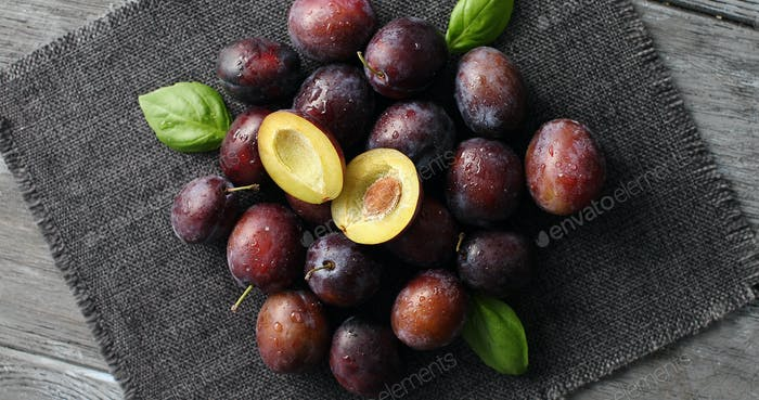 Served ripe plums on napkin