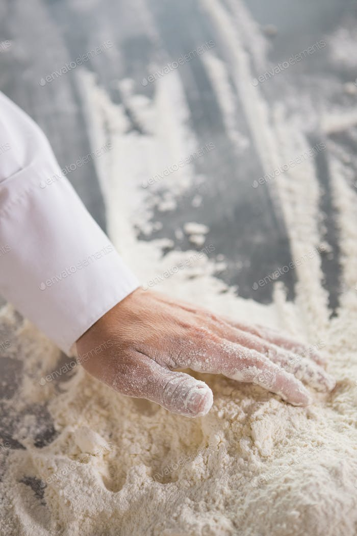 Close up of baker preparing dough in the kitchen of the bakery