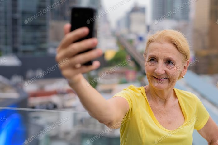 Beautiful senior woman taking selfie with mobile phone in city