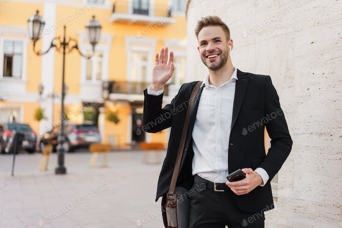 Joyful businessman in earphones waving hand and holding mobile phone