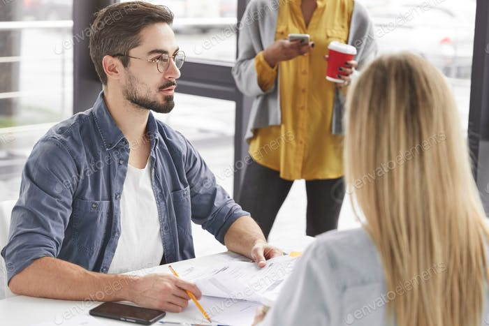 Three coworkers or colleagues plan together productive working process, sit in office interior, try