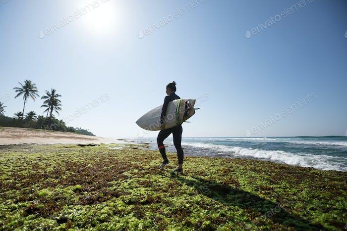 Surfer with surfboard on seaside