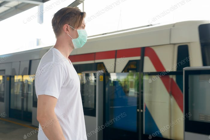 Profile view of young man with mask for protection from corona virus outbreak at the train station