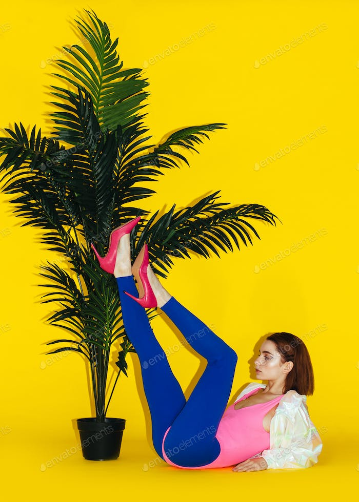 young modern female model near palm isolated on yellow background