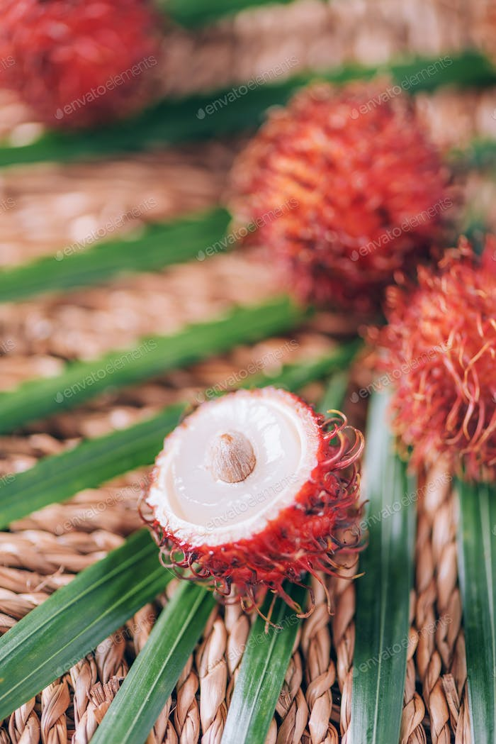 Rambutan fruits with palm leaves on rattan background. Top view. Copy space. Tropical fruit