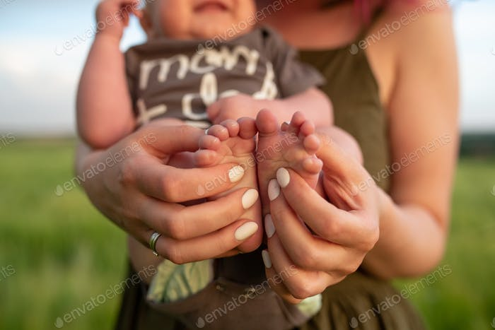 A mother holds the legs of her little three month old baby boy. Close-up.