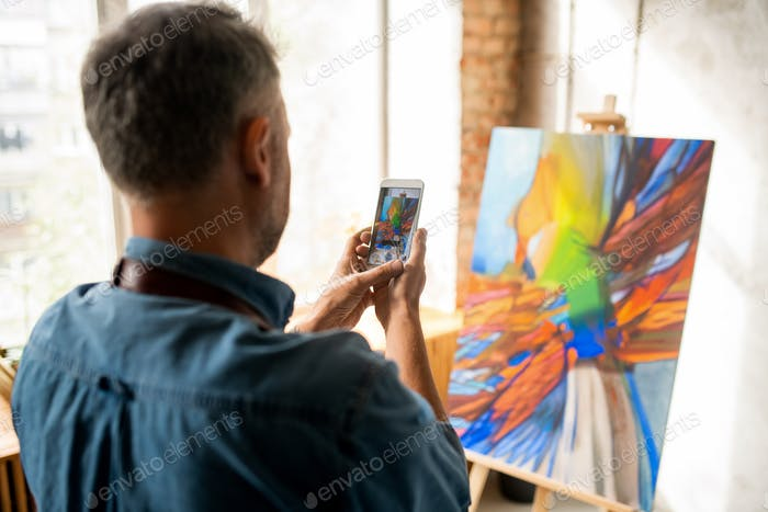Creative man standing in front of painting while taking its photo on smartphone