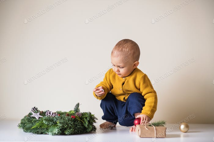 A toddler boy and a Christmas wreath on a table.