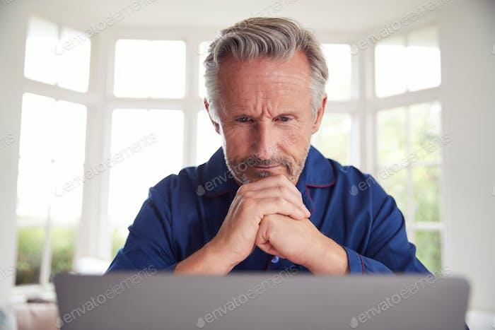 Serious Mature Man Looking Up Information Online Using Laptop