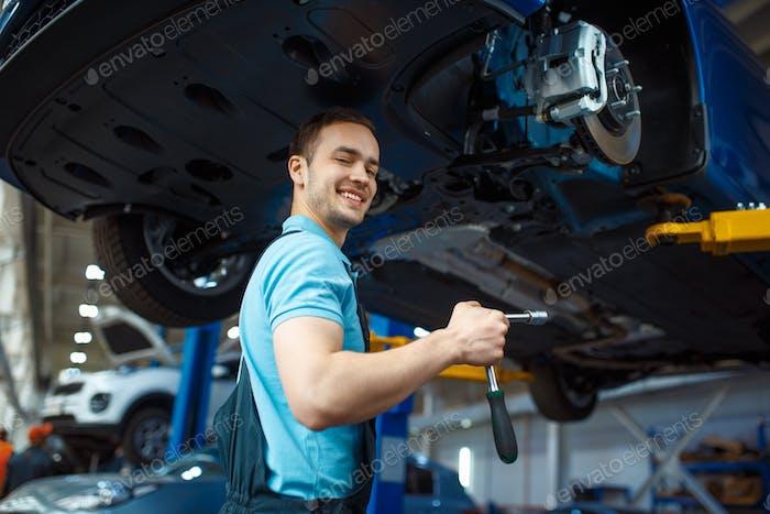 Repairman repairing vehicle on lift, car service