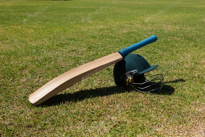 High angle view of cricket bat and helmet on field