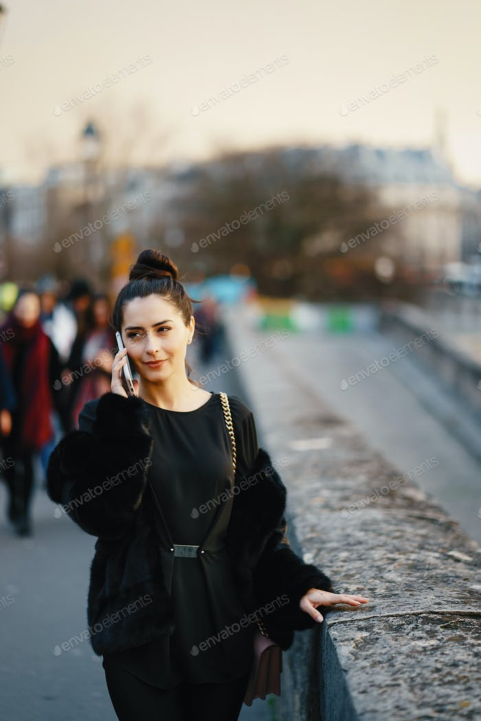 woman using her cell phone while walking through Paris