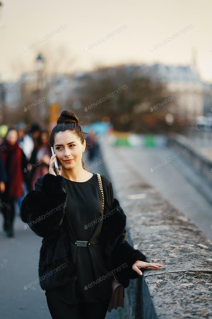 Frau mit ihrem Handy beim Gehen durch Paris