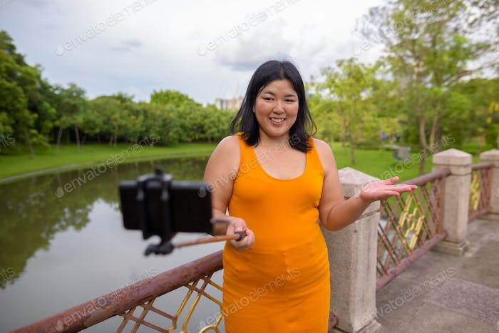 Asian woman taking selfie with mobile phone attach to selfie stick in park