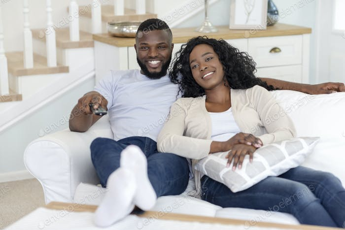 Smiling african american couple relaxing and watching TV at home