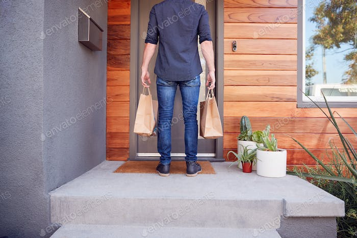 Rear View Of Home Delivery Service Driver Standing Outside Front Door With Takeaway Food Bags