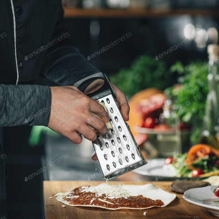 Preparing Vegetarian Burrito - Chef Grating Cheese with a Grater